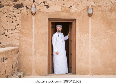 omani man in traditional outfit going out from the mai door of his traditional House