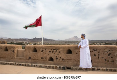 omani man in traditional outfit looking at the landscape of countruside