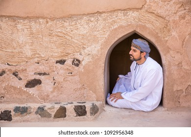 omani man in traditional outfit in an old omani house