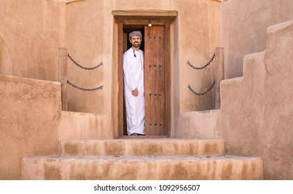 omani man in traditional outfit in an old house