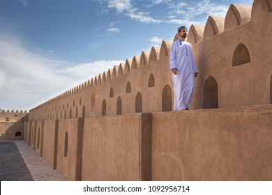 omani man in traditional outfit walking on a wall of Jibreen castle
