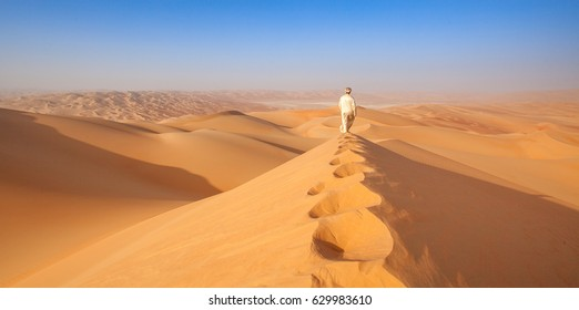 Omani Man walking over sand dune in the empty quarter