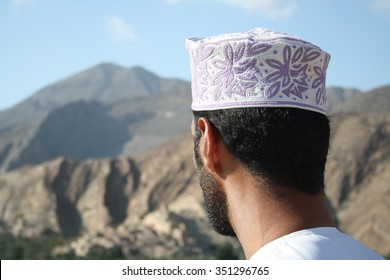 Omani Man wearing traditional head dress looking across mountains