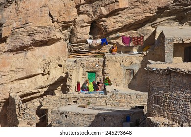 Omani women relaxing outside a traditional stone house in a small cliff hamlet near Sroot in the Jebel Akhdar mountains of the Sultanate of Oman.