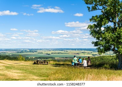 Omberg, Sweden – July 1, 2018: Visitors in the eco park enjoying the fantastic view over the Swedish landscape from the viewpoint Hjassan on an ordinary sunny summer day.