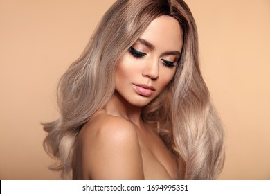 Ombre blond wavy hairstyle. Beauty fashion blonde woman portrait. Beautiful girl model with makeup, long healthy hair style posing isolated on studio beige background.