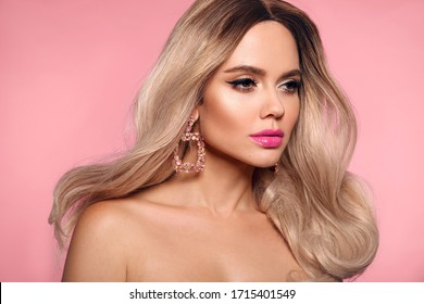 Ombre blond wavy hairstyle. Beauty fashion blonde woman portrait. Beautiful girl model with makeup, long healthy hair style posing isolated on studio pink background.