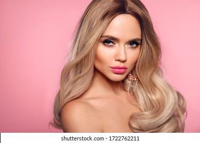 Ombre blond wavy Frisur. Schönheit Mode blonde Frau Porträt. Schönes Mädchenmodell mit Make-up, langes, gesundes Haar-Stil, das einzeln auf rosafarbenem Studiohintergrund steht.