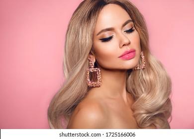 Ombre blonde Wavy Frisur. Schönheit Mode blonde Frau Portrait. Schönes Mädchen Modell mit Make-up, lange gesunde Haare Stil, die isoliert auf Studio rosa Hintergrund posiert.