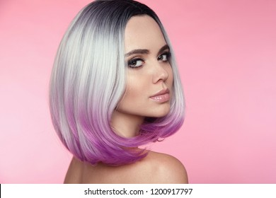 Ombre bob short hairstyle. Beautiful hair coloring woman. Trendy puprle haircut. Blond model with short shiny haircuts isolated on pink Background. Makeup. Beauty Salon.