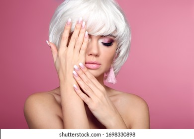 Ombre manicure nails. Blond bob short hairstyle. Hands. Beautiful hair coloring woman. Trendy haircuts. Blonde model with short shiny hairstyle isolated on pink studio background. Beauty Salon.