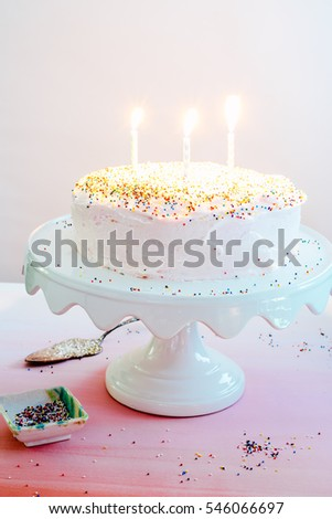 An Ombre Vanilla Pink Birthday Cake On White Stand With Multicolored Sprinkles Lit Candles