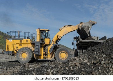 """Omchak, Russia - August 15, 2019. The work of mining machinery """"Komatsu"""" at the polygon in the city of Omchak."""
