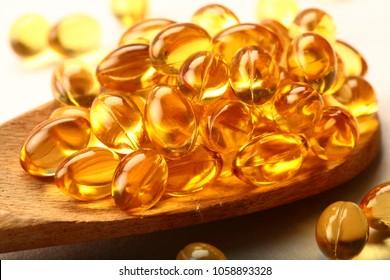 Omega 3 cod live fish oil pills in spoon .health care and medicine concept.