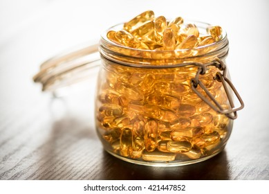 Omega 3-6-9 fish oil yellow softgels on wooden black board into airtight glass jar
