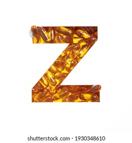 Omega supplement. Letter Z of alphabet of oil fish pills and paper cut isolated on white. Golden typeface for pharmacy