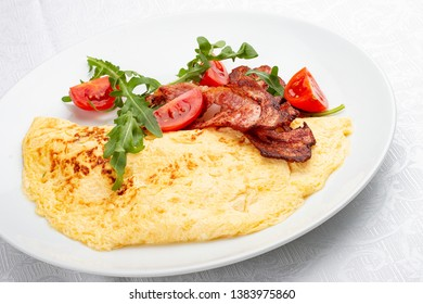Omelet with bacon and tomatoes on white background