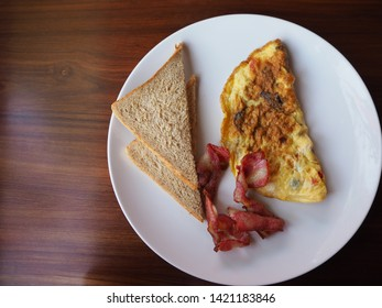 Omelet and bread with bacon on wooden table. Plate of breakfast with omelet, bacon and toasts. top view