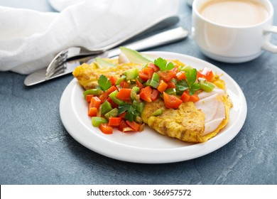 Omelet for breakfast with ham, bell peppers and avocado