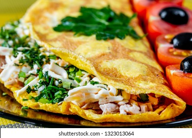 Omelet of chicken eggs stuffed with chicken meat with cheese and herbs. A tasty and healthy Breakfast is served with cherry tomatoes and black olives. The concept of proper nutrition and diet