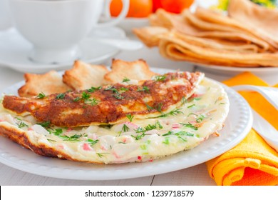 Omelet with crab sticks on a white plate with toast of white bread, horizontal