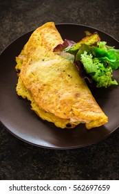 Omelet and green salad on ceramic plate.Stone background Selective focus.