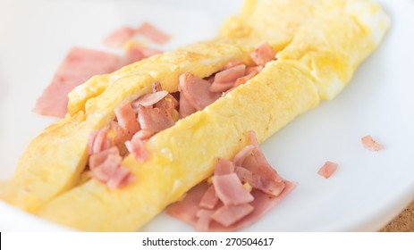 Omelet with ham on white dish