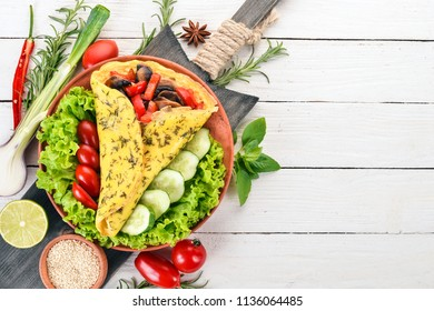 Omelet with mushrooms and vegetables. Fried eggs. On a wooden background. Top view. Free copy space.