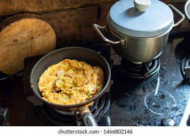 Omelet or omelette is cooking in a pan. It is popular street food in Thailand. In a photo is Omelet in Thai style. The kitchen is dirty.