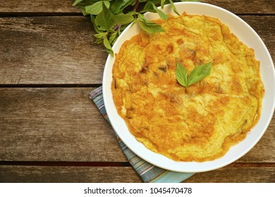 Omelet (omelette, Scrambled) with basil on wood table. Easy to cook. Put little soy sauce, sugar and pepper. Famous food in Thailand. Still life food. Vegetarian. Copy space.