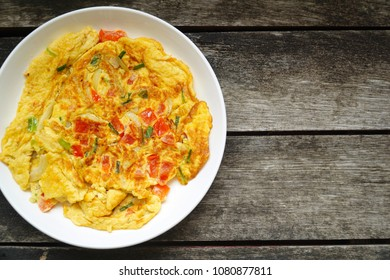 Omelet (Omelette, Scrambled) with Tomato, Carrot, green onion on white plate. Fresh ingredient. Quick meal. Vegetarian. Still life food. Yummy. Copy space.