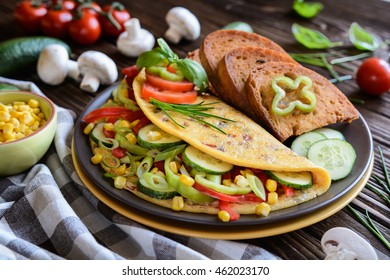 Omelet with pepper, tomato, corn, green onion, cucumber, mushrooms and fried bread on a wooden background