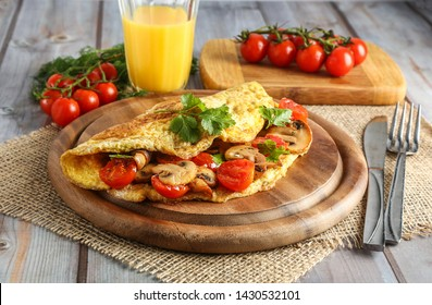 Omelet or scrambled eggs on a plate with cherry tomatoes, mushrooms, coriander and orange juice.