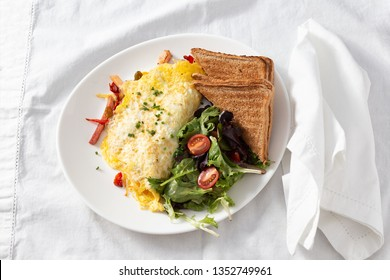 omelet with side salad and toasts. healthy breakfast on the table. top view