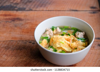 Thai omelet with soup on wooden table