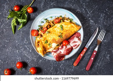 Omelet with tomatoes, mushrooms and bacon. Breakfast on stone background. Top view.