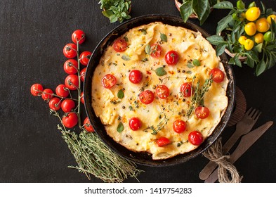 Omelet with tomatoes, parsley and cheese on a cast iron pan on a black wooden table. The view from the top. Copy space.