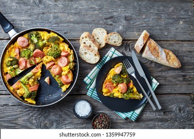 omelette with broccoli and sausages in a skillet and served on a plate on an old grey rustic wooden table with sliced crusty wholegrain French baguette, view from above, flat lay