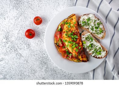 Omelette with cherry tomatoes, toasts with cream cheese and greenery. Healthy food concept.