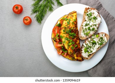 Omelette with cherry tomatoes, toasts with cream cheese and greenery