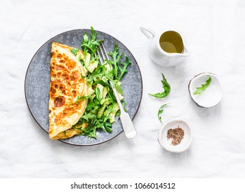 Omelette with cream cheese, arugula and avocado salad on a light background, top view.  Healthy breakfast or diet lunch