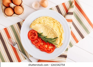 Omelette Egg with Slice Tomato Top Down View. Fried Omelet in White Plate for Healthy Morning Lunch. Delicious Scrambled Dish with Fresh Vegetable Macro Shot