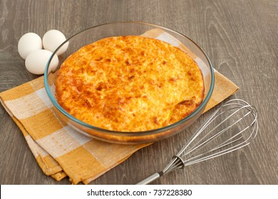 Omelette and eggs. A large baked omelette in a glass bowl. Raw eggs for making an omelette. A golden omelette crust. Dish of eggs for breakfast. Protein in an omelet.