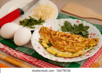 Omelette in French and its ingredients. Grated cheese, chopped parsley, eggs are needed to prepare a French omelet. Omelette in French on a kitchen towel. Cooked breakfast of eggs.