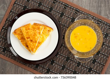 Omelette and mixture for omelet. A mixture of eggs and milk to make an omelet. Pieces of omelette with golden crust. View from above. Baked omelette for breakfast.