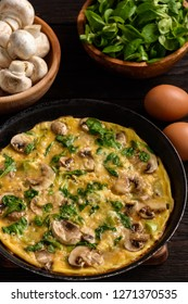 Omelette with mushrooms and cheese, on dark wooden background.