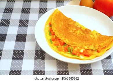 Omelette (Omelet, Scrambled) with cherry tomatoes, onion, carrot, green onion and grated cheese. Fresh ingredient. Easy to cook. Good for breakfast. Copy space. Delicious. Still life food.
