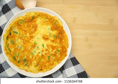 Omelette (Omelet, Scrambled) with green onion served on wood table. Vegetarian. Still life food. Popular in Thailand. Copy space.