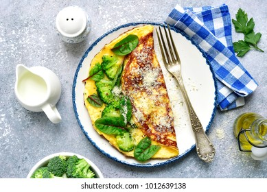 Omelette stuffed with broccoli, cheese and chard leaves for a breakfast on a white plate over light grey slate, stone or concrete background.Top view.