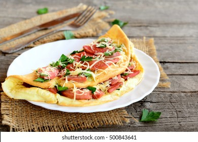 Omelette stuffed with fried sausages, grated cheese and parsley on a plate, fork, knife and an old wooden table. Eggs breakfast